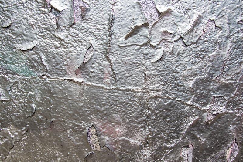O fundo da textura do estuque Fragmento de uma parede velha com pintura de prata Casca da pintura de prata imagens de stock
