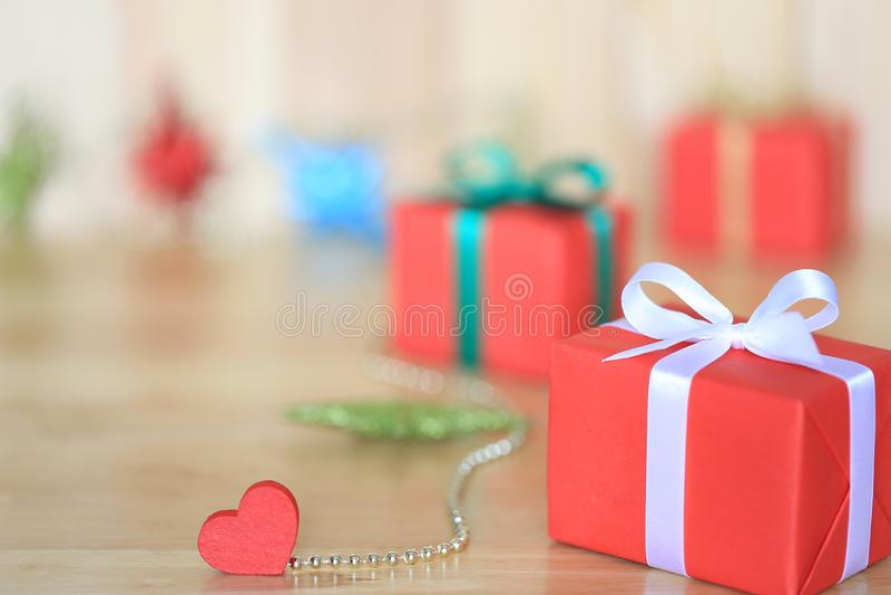 O fundo de ano novo para a estação do Natal ou do cumprimento, caixa de presente vermelha com fita branca e coração vermelho no f foto de stock