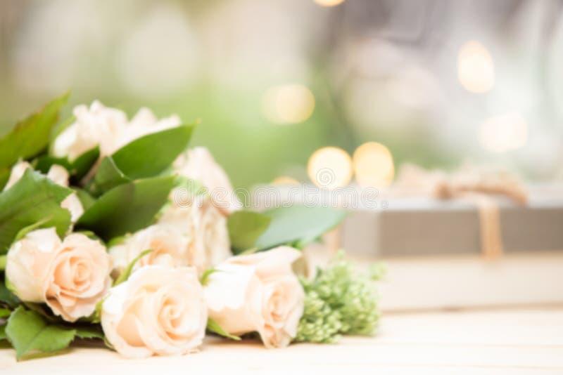 O fundo do borrão aumentou flor na tabela de madeira com espaço da caixa de presente e da cópia fotografia de stock