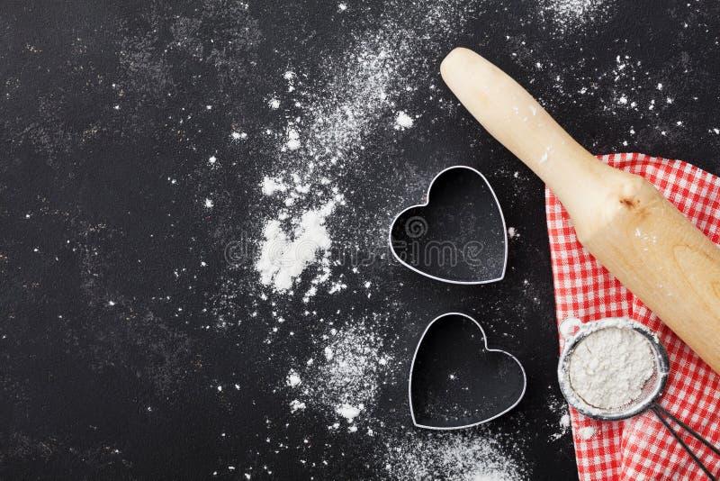 O fundo do cozimento com farinha, o pino do rolo e o coração dão forma na opinião de tampo da mesa do preto da cozinha para o coz fotografia de stock royalty free