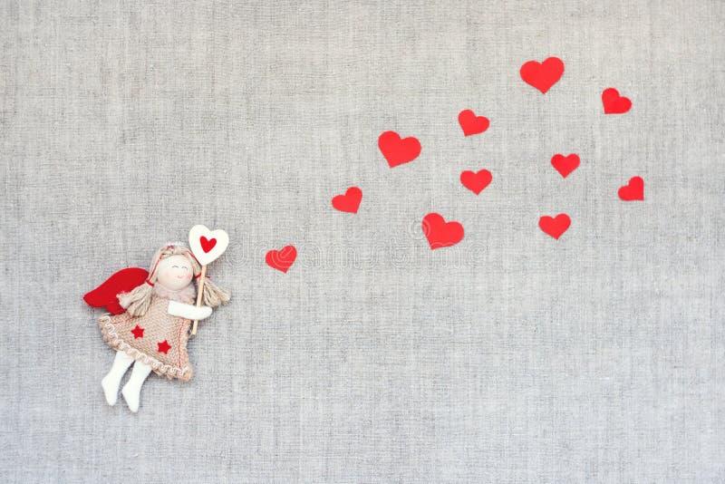 O fundo do dia de Valentim com fada do anjo do ofício do brinquedo e muitos corações vermelhos nublam-se a forma na tela de linho foto de stock royalty free