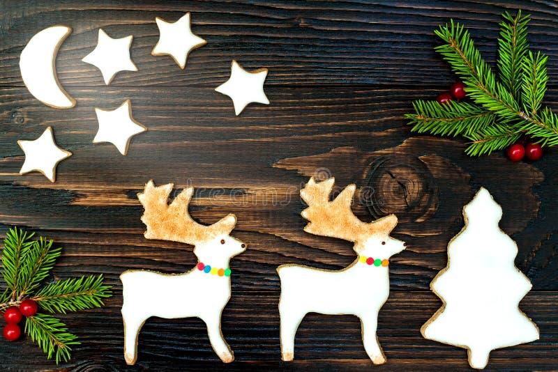 O fundo do feriado do Natal com cookies e abeto do pão-de-espécie ramifica na placa de madeira velha Copie o espaço foto de stock