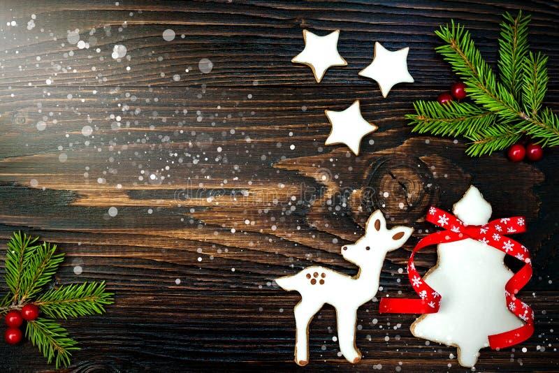 O fundo do feriado do Natal com cookies e abeto do pão-de-espécie ramifica na placa de madeira velha Copie o espaço fotografia de stock