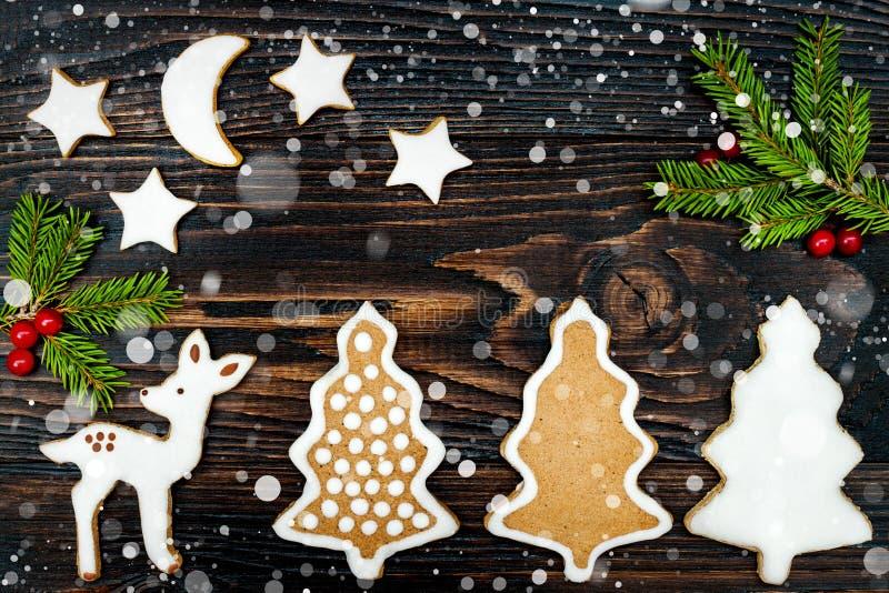 O fundo do feriado do Natal com cookies, especiarias e abeto do pão-de-espécie ramifica na placa de madeira velha Copie o espaço fotos de stock