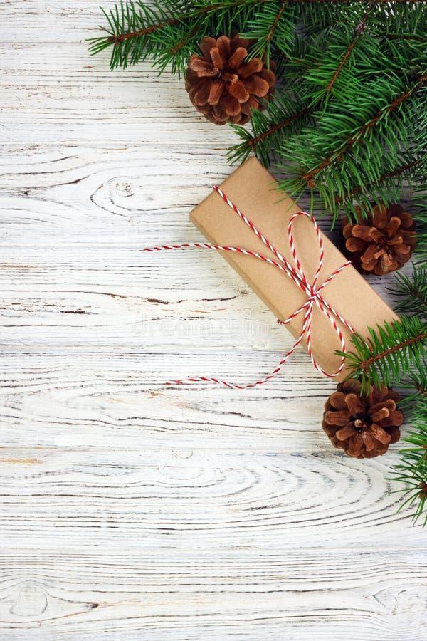 O fundo do Natal com o presente do Natal no fundo de madeira com abeto ramifica Composição do Xmas e do ano novo feliz Vista supe fotografia de stock