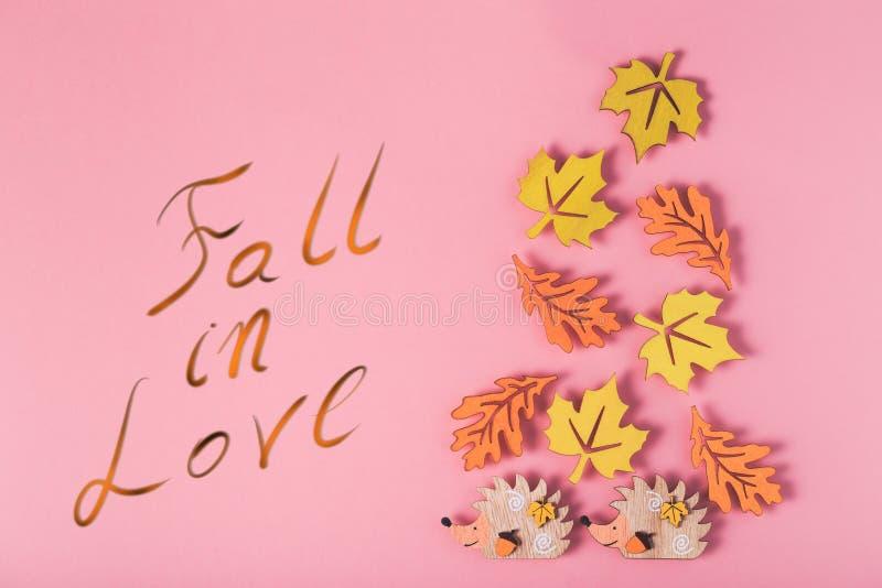 O fundo do outono com figuras de madeira multicoloridos sae e ouriços e queda da inscrição no amor imagem de stock