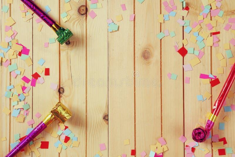 O fundo do partido com confetes coloridos e o partido assobiam imagens de stock