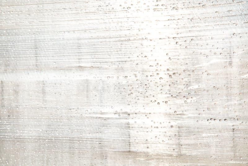 O fundo do polietileno esticado com os pingos de chuva iluminados pelo sol lá é um lugar para o texto fotos de stock