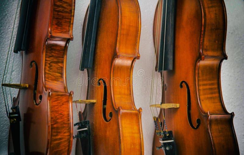 O fundo do projeto da arte abstrato de três violinos empilhados no fundo mostre o lado da madeira no estilo do violino, do vintag fotografia de stock royalty free