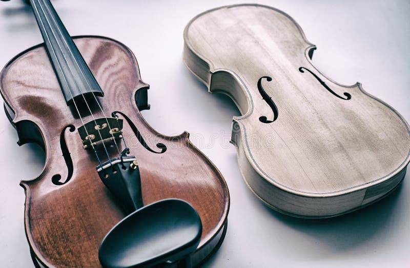 O fundo do projeto da arte abstrato do violino cru pôs ao lado do violino terminado foto de stock