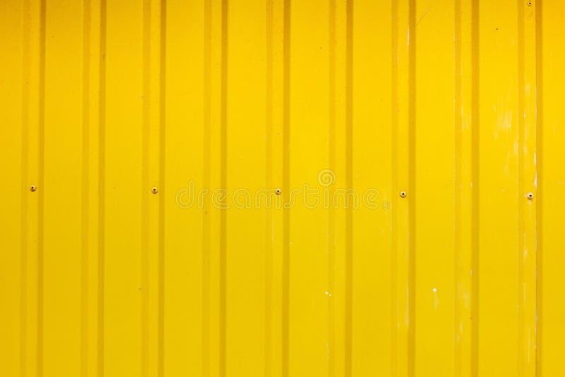 O fundo do sumário corrugou o metal cinzento para a parede, pintura amarela material imagem de stock