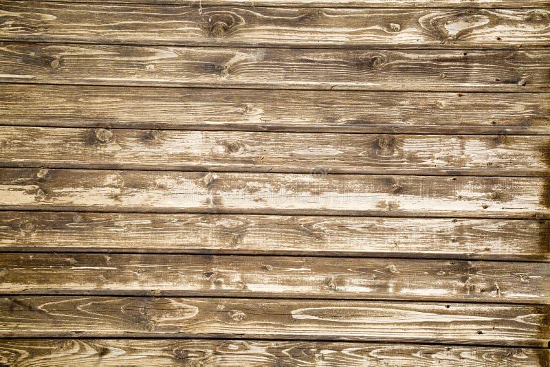 O fundo está em placas de planeamento idosas com uma estrutura pronunciada dos redemoinhos de madeira fotos de stock royalty free