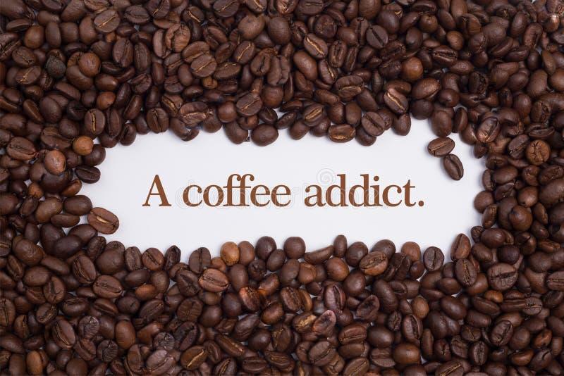 O fundo fez de feijões de café em uma forma do coração com o viciado do café do ` A da mensagem ` imagens de stock royalty free