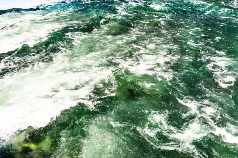 O fundo fez de uma pressa, de um rio espumoso em uma turquesa bonita e de uma cor verde foto de stock
