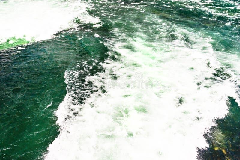 O fundo fez de uma pressa, de um rio espumoso em uma turquesa bonita e de uma cor verde imagens de stock