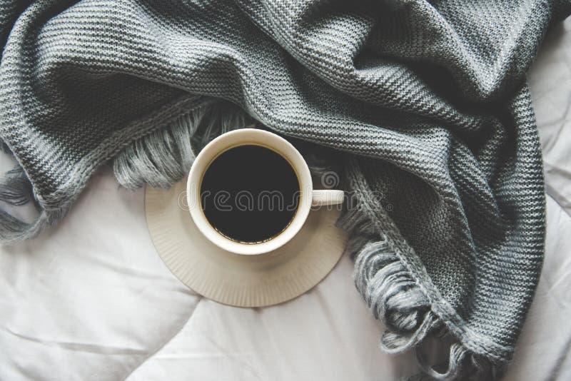 O fundo home do inverno acolhedor, copo do café quente com marshmallow, aquece a camiseta feita malha no fundo branco da cama, to fotografia de stock royalty free
