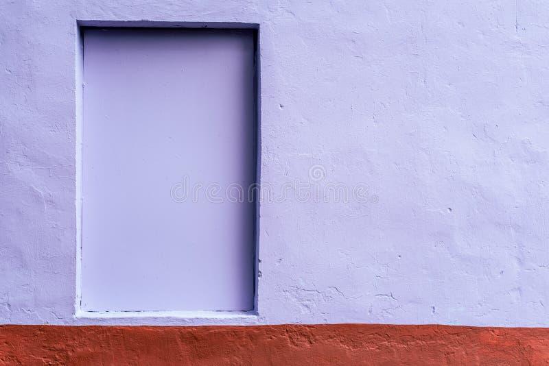 O fundo homogêneo da parede é tingido com uma pintura marrom e roxa Janela escondida O fundo do foto de stock