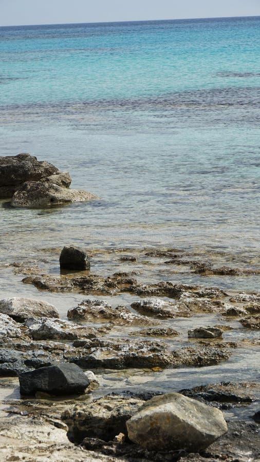 O fundo o mar azul e as rochas encalha em Chipre no verão fotos de stock royalty free