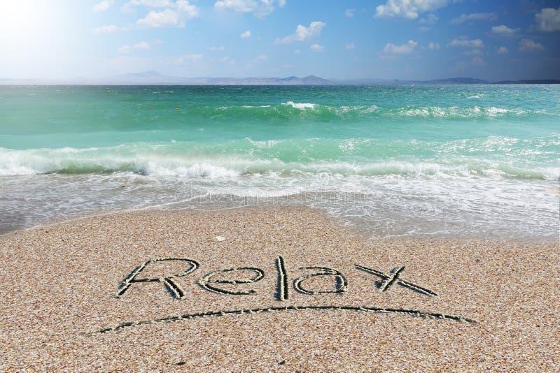 O fundo ou o papel de parede do feriado com relaxam palavra escrita à mão na areia da praia imagem de stock