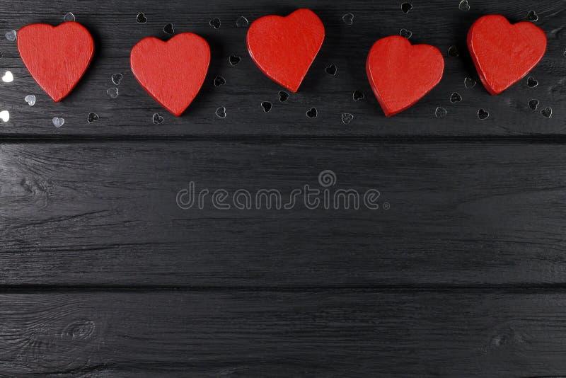 O fundo romântico com corações de madeira vermelhos em um fundo preto foto de stock