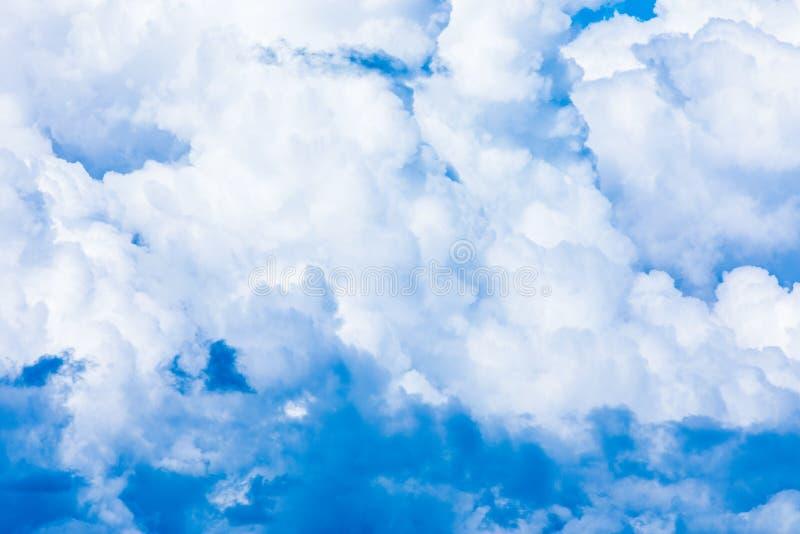 O fundo vívido do céu ou do céu com as nuvens brancas sob os raios do sol imagem de stock