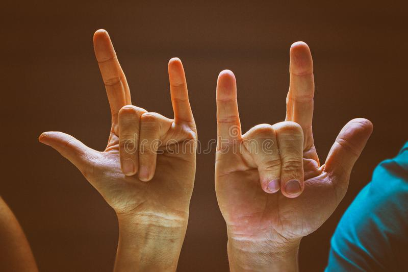 O fundo velho clássico do projeto do filme das mãos humanas no sinal e no symbo do rock and roll foto de stock royalty free