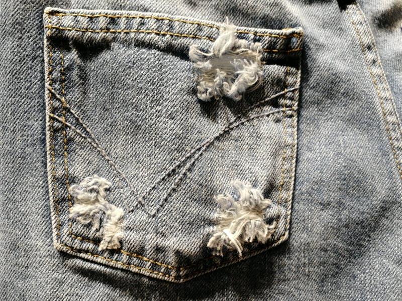 O furo fez especialmente pelo fabricante no bolso traseiro da roupa da sarja de Nimes foto de stock