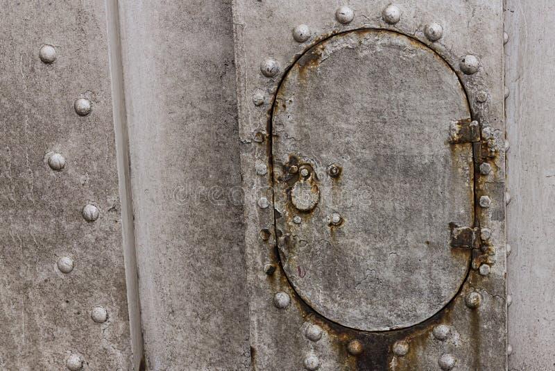O furo técnico oval do portal do ferro na superfície cinzenta do fundo rebita o projeto industrial da base oxidada castigado pelo fotos de stock