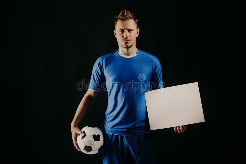 O futebol considerável novo do jogador de futebol guarda a bola e a placa branca no branco imagens de stock