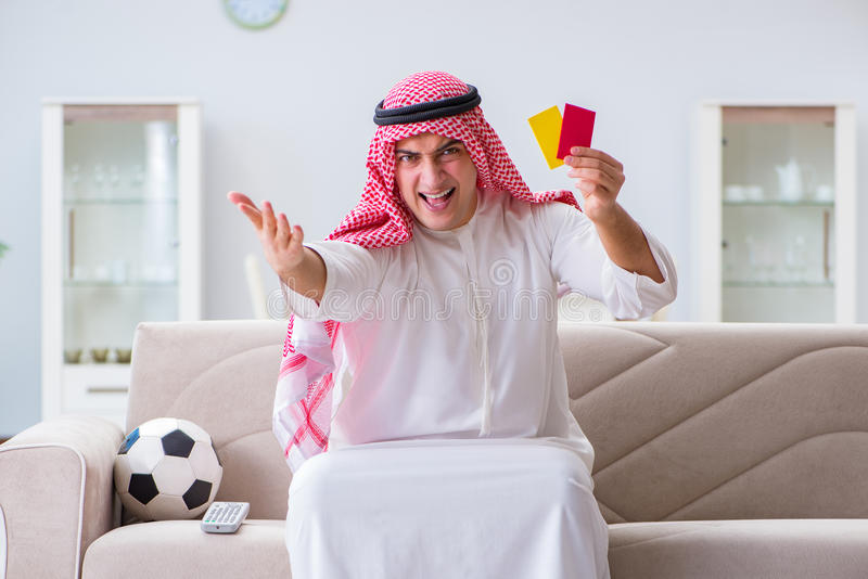O futebol de observação do esporte do homem árabe na tevê fotos de stock