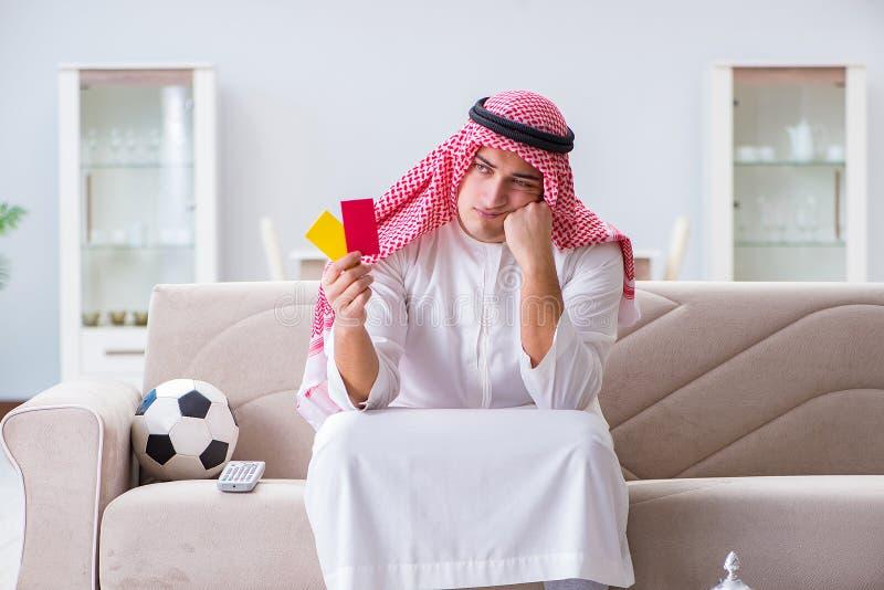O futebol de observação do esporte do homem árabe na tevê fotografia de stock