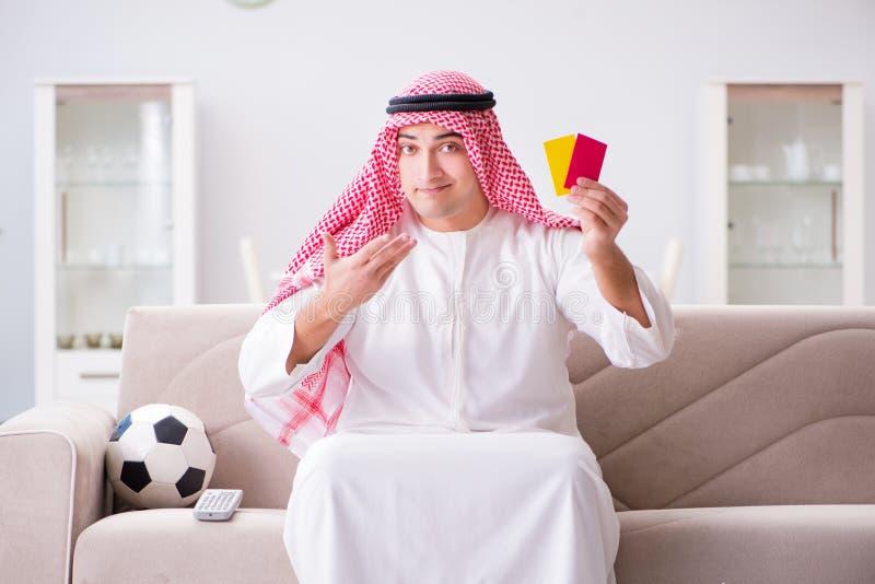 O futebol de observação do homem árabe novo que senta-se no sofá foto de stock