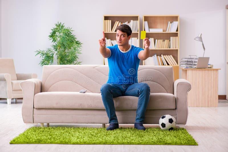 O futebol de observação do homem em casa que senta-se no sofá fotografia de stock royalty free