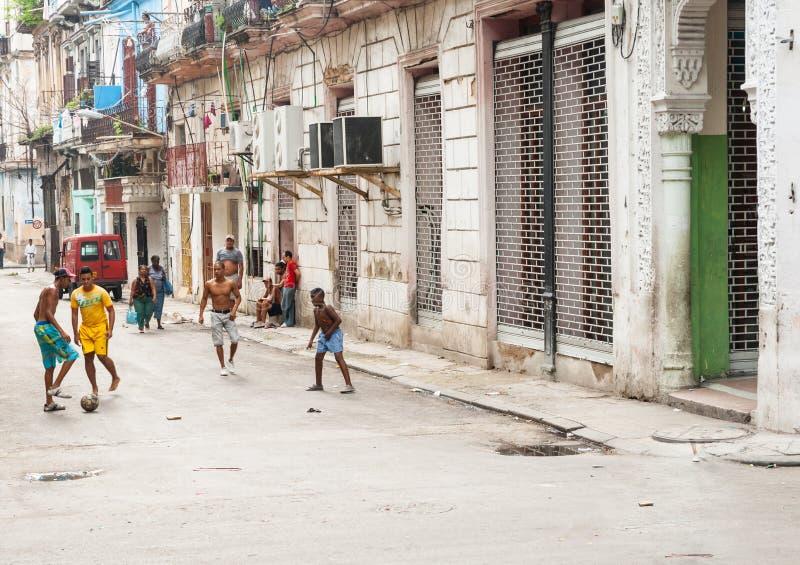 O futebol do jogo de quatro meninos na rua urbana como povos anda pelo surrou fotos de stock