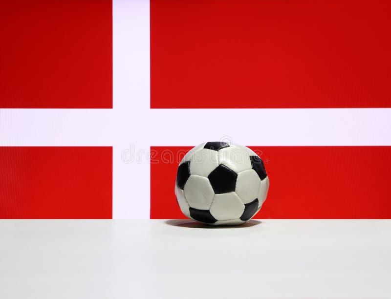O futebol pequeno no assoalho branco e a cruz branca no vermelho da nação de Dinamarca embandeiram o fundo foto de stock royalty free