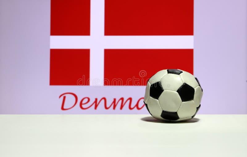 O futebol pequeno no assoalho branco e a cruz branca no vermelho da nação dinamarquesa embandeiram o fundo com texto de Dinamarca fotos de stock