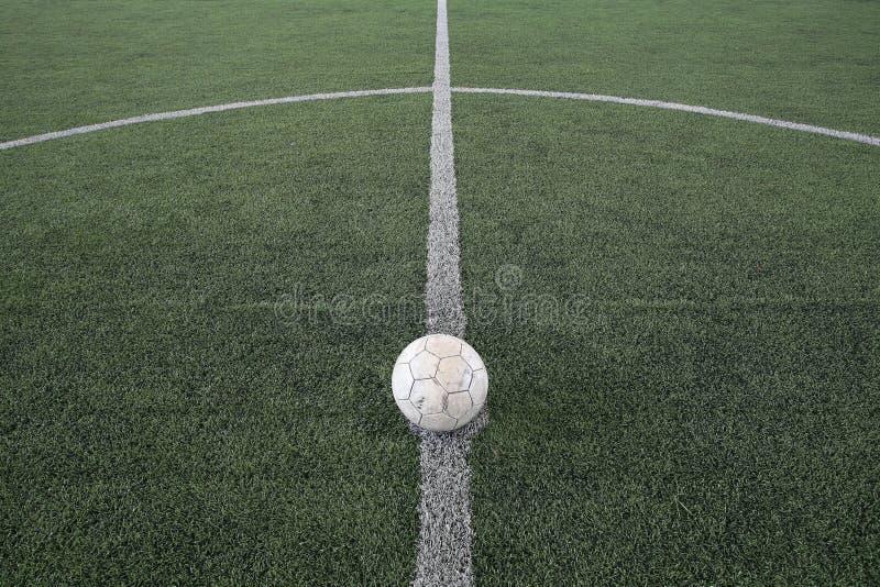 O futebol velho em retrocede fora a marca na grama falsificada foto de stock royalty free