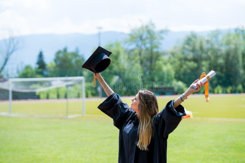 O futuro do abraço da menina do aluno diplomado e olha acima ao céu, ela veste a GR fotografia de stock royalty free