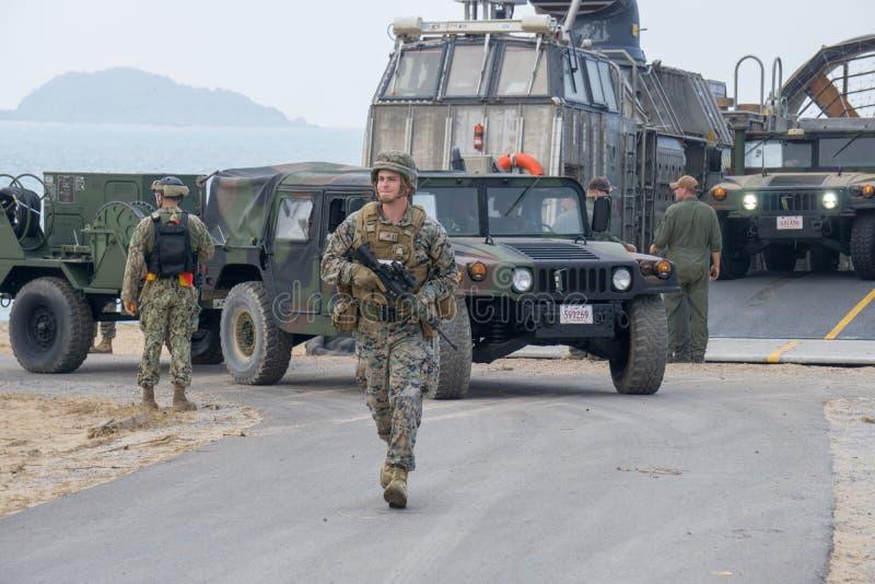 O fuzileiro naval dos E.U. no uniforme da camuflagem da selva anda na estrada para conduzir um humvee à área de estacionamento imagens de stock