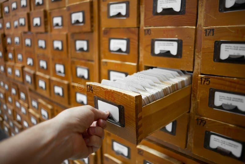 O gabinete da base de dados e a mão humana abrem a gaveta de cartão imagens de stock