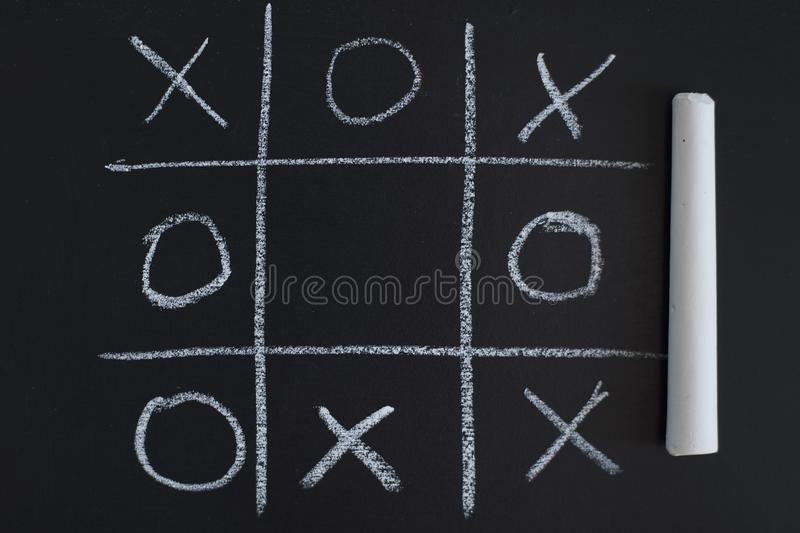 O X Game on black chalk board royalty free stock image