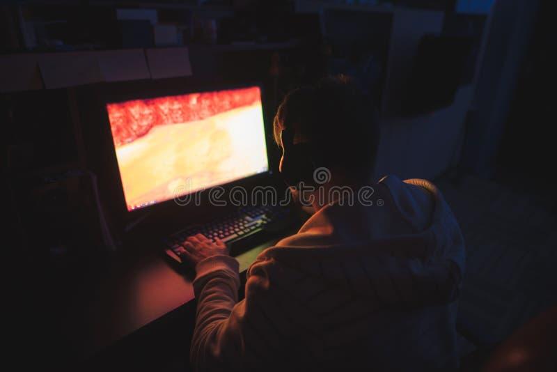 O gamer focalizado senta-se no computador em casa na sala acolhedor e joga-se jogos do horror no computador imagem de stock