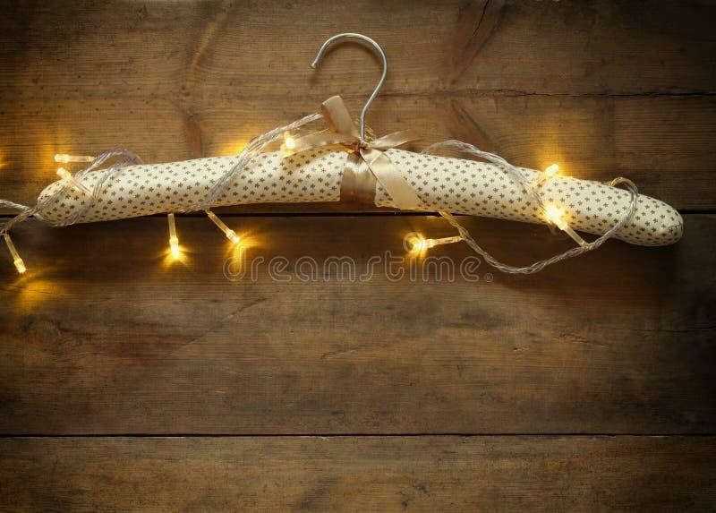 O gancho da tela do vintage com a festão morna do ouro do Natal do ouro ilumina-se no fundo rústico de madeira Imagem filtrada imagem de stock royalty free
