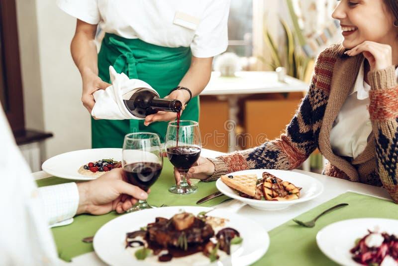 O garçom da menina derrama o vinho a um par no amor fotografia de stock royalty free