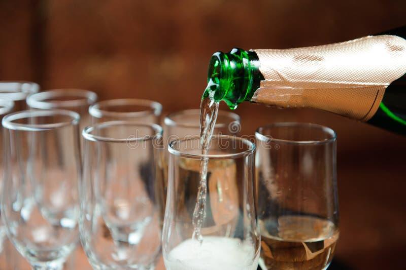 O garçom derrama o champanhe nos vidros na tabela imagem de stock