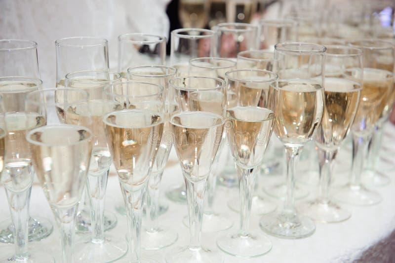 O garçom derrama o champanhe nos vidros na tabela fotografia de stock
