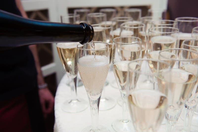 O garçom derrama o champanhe nos vidros na tabela imagem de stock royalty free