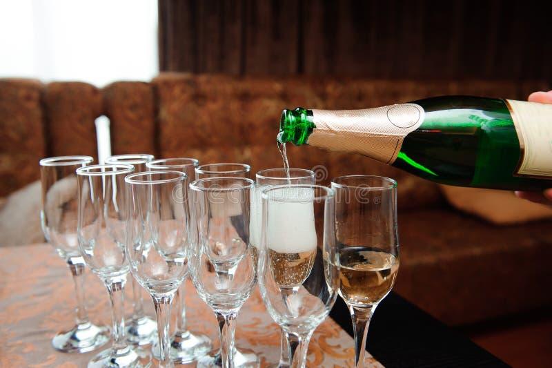 O garçom derrama o champanhe nos vidros na tabela fotos de stock royalty free
