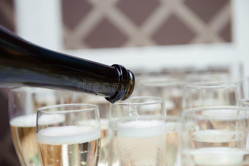O garçom derrama o champanhe nos vidros na tabela imagens de stock royalty free