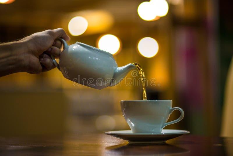 O garçom derrama o chá no copo imagens de stock